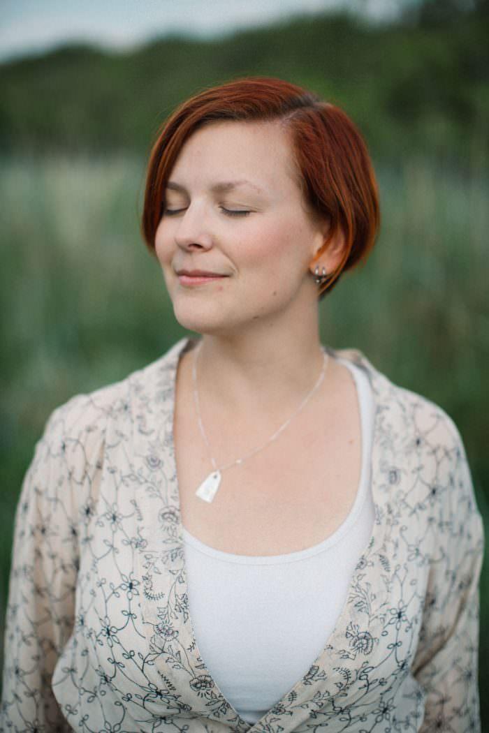 Enskilt porträtt på kvinna som blundar. Somrig bakgrund.