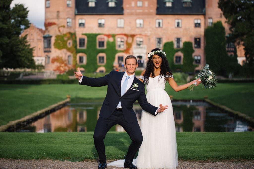 Ett glatt brudpar firar sitt bröllop utanför Trolleholms Slott. Foto av Tove Lundquist, bröllopsfotograf Skåne.