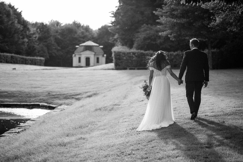 Svartvitt foto på ett gående brudpar utanför Trolleholms slott. Foto av Tove Lundquist, bröllopsfotograf Skåne.